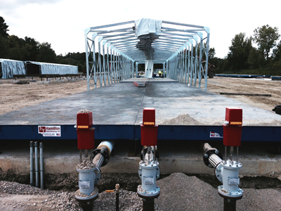 CAPTION: Preliminary New NY Bridge contract work has seen Unistress crews run steam lines with actuator valves and power to deck panel casting beds, secure collapsible tent enclosures, and test specimens.
